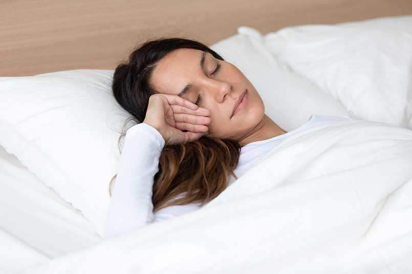 Peaceful mixed race young woman sleeping alone in bed.