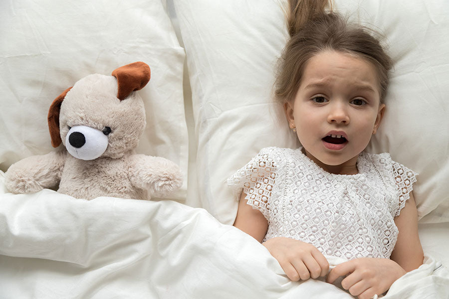 Scared child lying in bed with toy afraid of nightmare