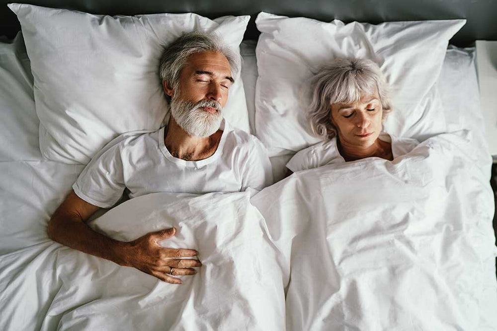 Senior family couple sleeping together in bed