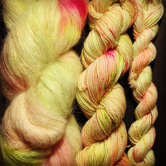 3 hanks of Orkney Range, hand dyed yarn in neon yellow with green and neon pink speckles and small splashes. Baby alpaca, sock weight and a mini sock weight hank.