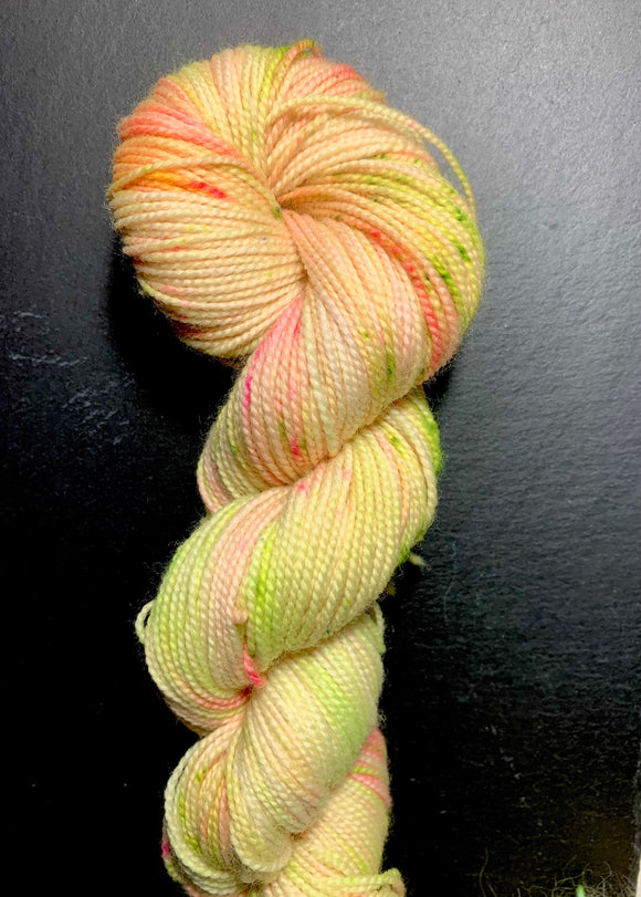 High twist 4ply, in neon yellow with splashes of neon pink and neon green, photographed in a twisted hank on black slate