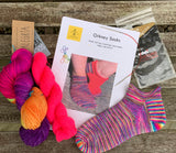 This is a knitting kit with an Orkney Sock knitting pattern, Addi sock Wunder circular needles, one 100g hank of rainbow Alegria yarn, one 50g hank Socks yeah yarn and 5 stitch markers. Photographed on a wooden garden bench
