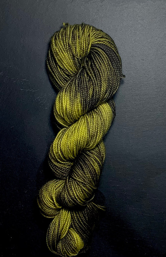 A twisted hank of high twist 4 ply yarn, with gradients of deep khaki to brighter khaki. Photographed on a black slate.