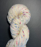 A twisted, 100g hank, of natural, undyed, Donegal yarn, with multi coloured nep. Yarn is draped over a piece of slate  Edit alt text
