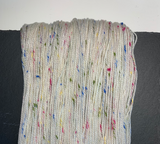 100g hank of natural, undyed, Donegal yarn, with multi coloured nep. Yarn is draped over a piece of slate
