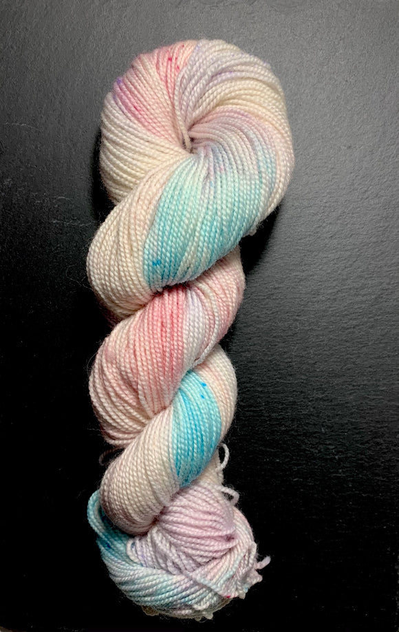 A twisted hank of high twist 4ply. the colours are a blend of pale pink and lilac, with splashes of turquoise and darker pink, with corresponding pink, lilac and turquoise speckles.