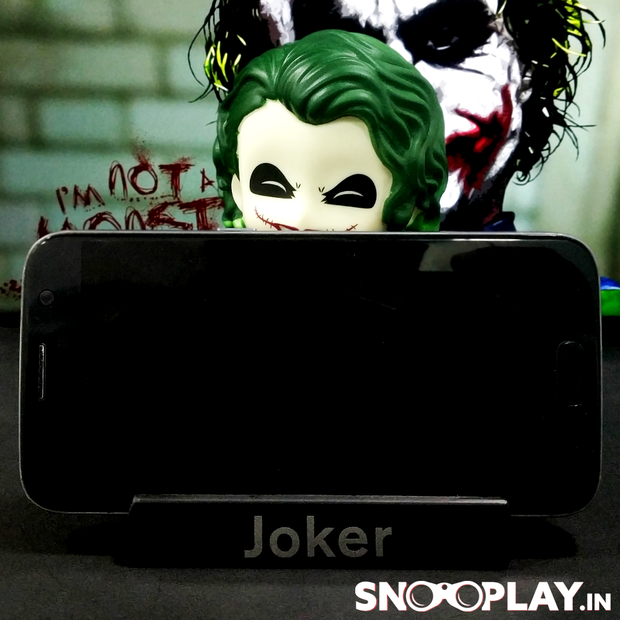 Joker bobblehead action figure for car decoration, holding a phone in its mobile stand,