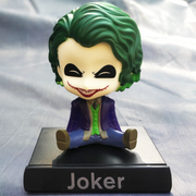 Joker bobblehead, a fictional character from the film, The Dark knight , with a phone stand. Ideal for decor purposes.