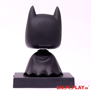 The back view of the batman bobblehead action figure, with an oversized head connected to the body by a spring.