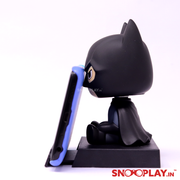 The side view of the batman bobblehead action figure, holding a phone stand.