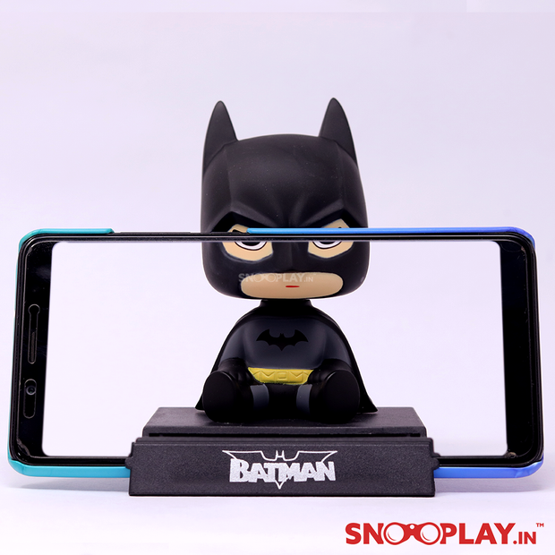 The batman bobblehead action figure, with an oversized head, been used as a phone stand.
