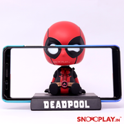 Deadpool Bobblehead action figure, holding the phone in its built in phone holder.