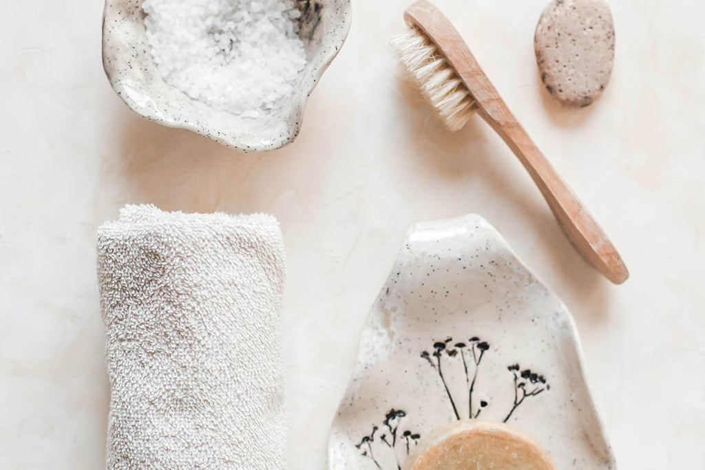 Dry brush for skin, himalayan salt, scrubber and face towel on marble