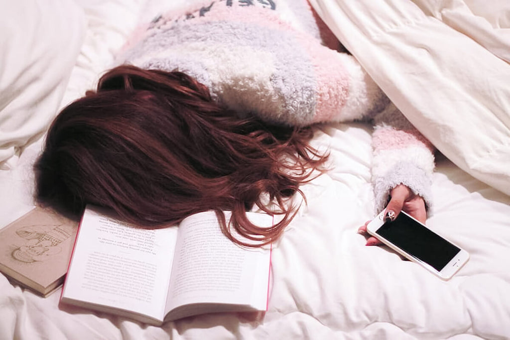 Girl sleeping on bed with phone