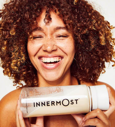 Lulu Stone laughing while holding an Innermost shaker bottle