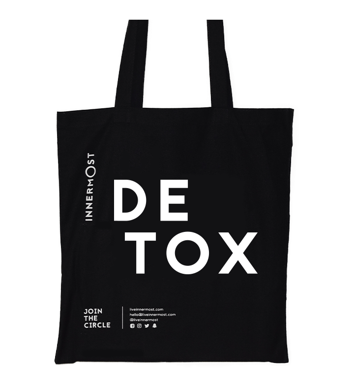 Innermost black cotton tote bag with DETOX printed on it