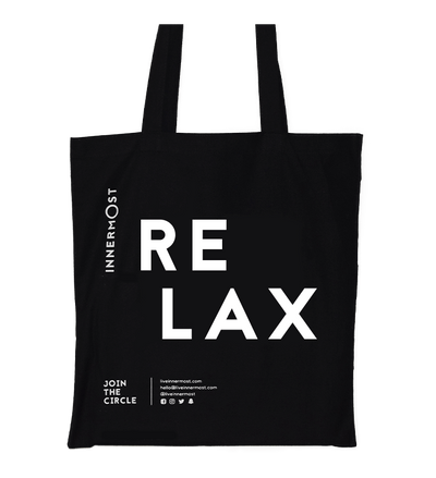Innermost black cotton tote bag with RELAX printed on it