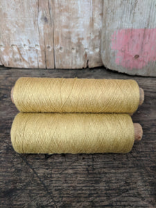 Vintage wooden bobbins with gold thread
