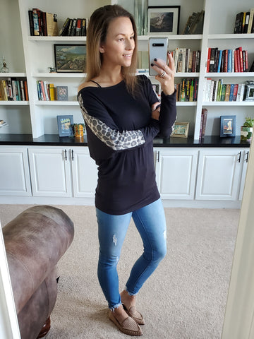 leopard stripe on sleeve of dolman style black tunic, lightly distressed skinny jeans, tan studded gold loafer shoes