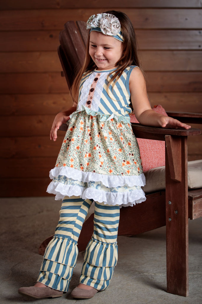 Precious delicate flowers , buttons and ruffles make up this 2 piece outfit. Soft colors of blue and lace detail this dress and pants. Sizes 2T-7T.