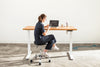 Woman sitting at a height adjustable wood desk