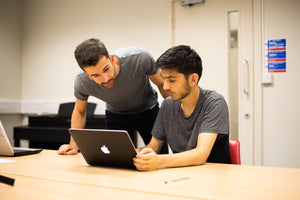 Tutor helps student with a problem on their computer as they prepare to apply to Oxford or Cambridge