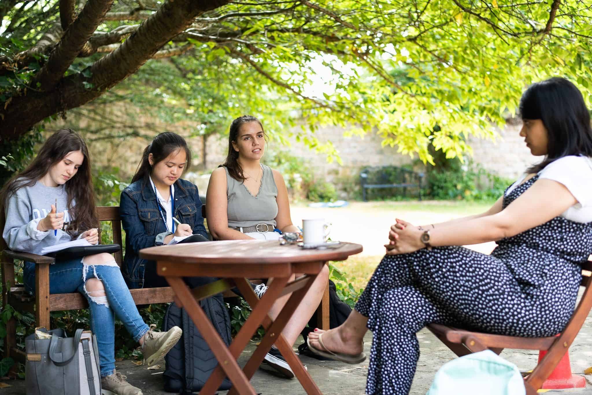 Students and tutors in a garden at oxford, talking about tips for the interview