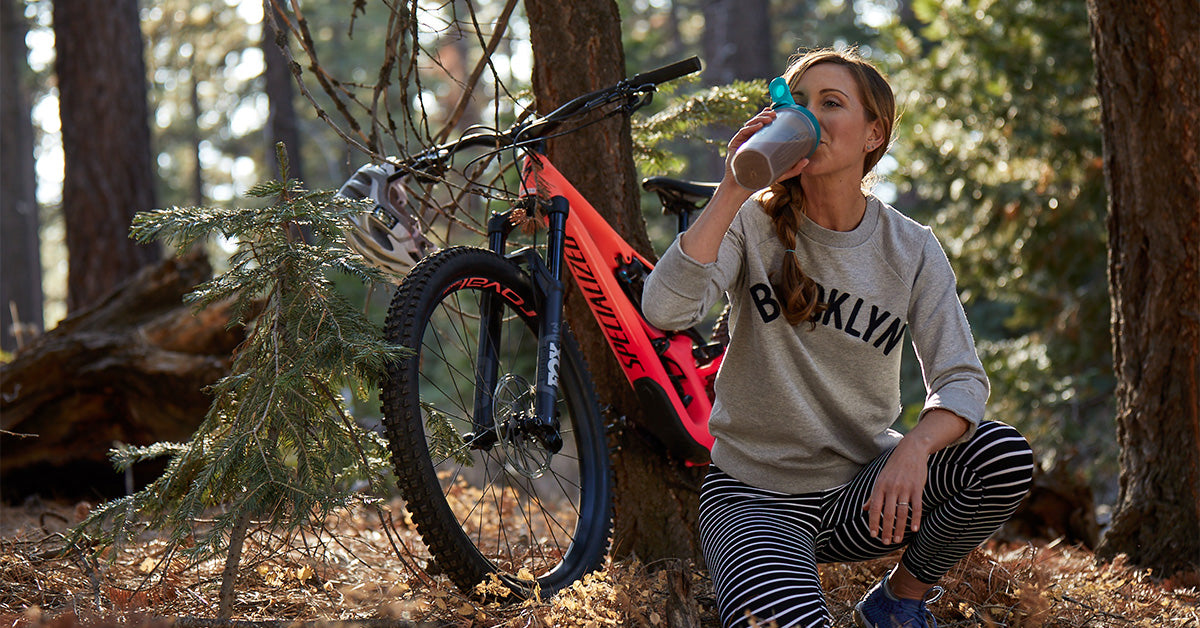 A woman with a mountain bike in the woods, taking a break to drink a superfood drink.