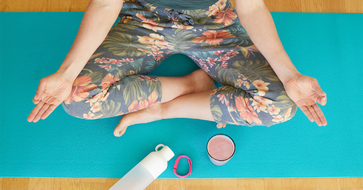 A woman meditating on a yoga mat with a superfood smoothie and water bottle