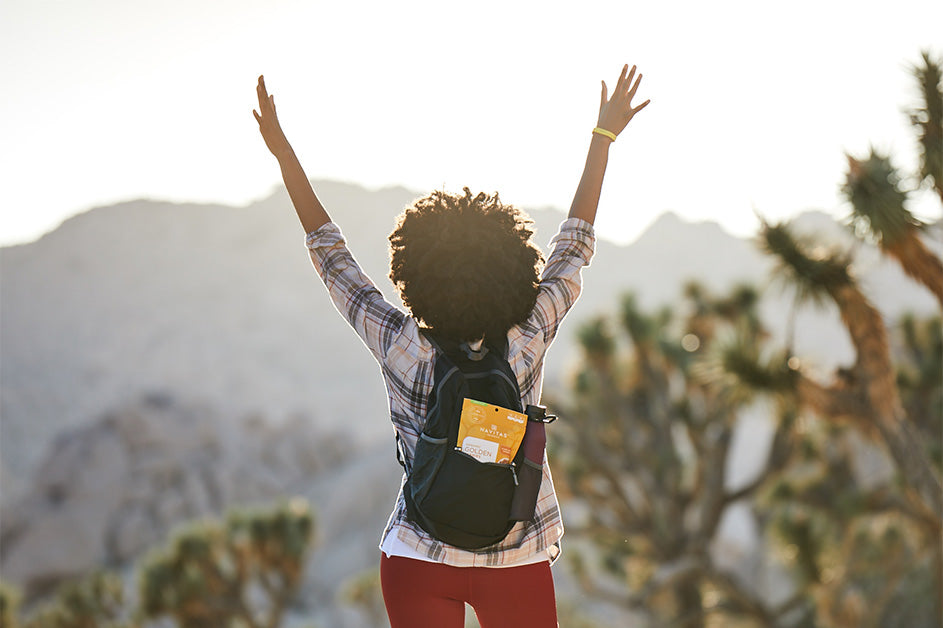 Woman in nature with backpack and Navitas Organics Goldenberries, raising hands