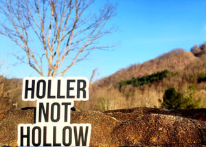 Holler Not Hollow Sticker in front of an outdoor view.