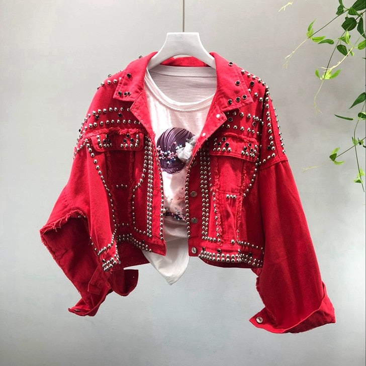 Studded Denim Jacket - Ellie J Shoppe. Oversized cropped jean jacket with distressed details and allover studs. Collar, buttons closure on front, chest pockets with flap and button, and buttons at cuffs. Details: Oversize fit Cotton Available in Black, Blue, and Red Hand Wash Cold