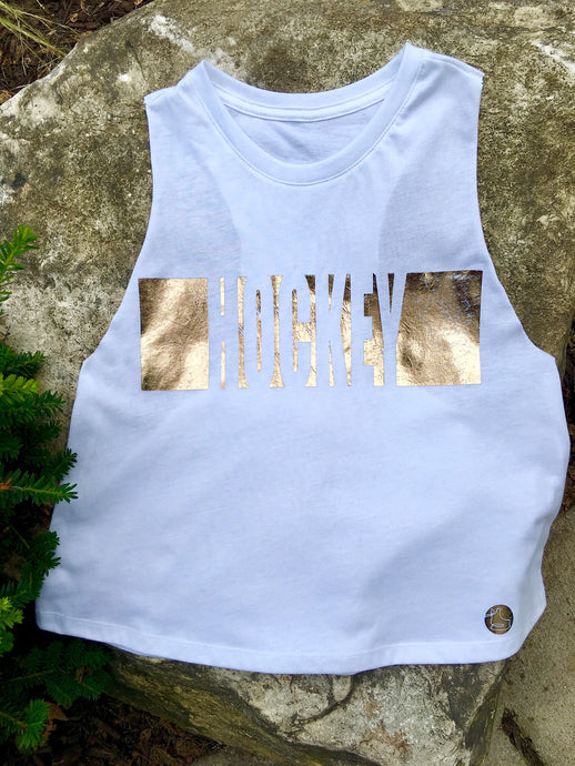 Cropped racer back tank in white with the word HOCKEY outlined in distressed gold metallic foil