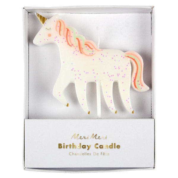 Glittering unicorn candle with colorful mane and tail and shiny gold foil
