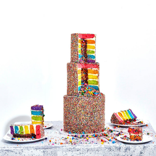 3 tiered cake. Each cake has 6 rainbow layers, cream cheese frosting, decorated with nonpareils and contain a sprinkle surprise in the center.