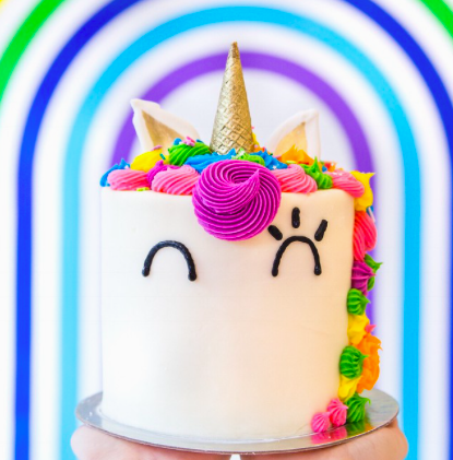 Cake decorated to look like Cara the Unicorn - 6 rainbow vanilla layers, cream cheese frosting, a ice cream cone horn, chocolate ears, and contain a sprinkle surprise in the center