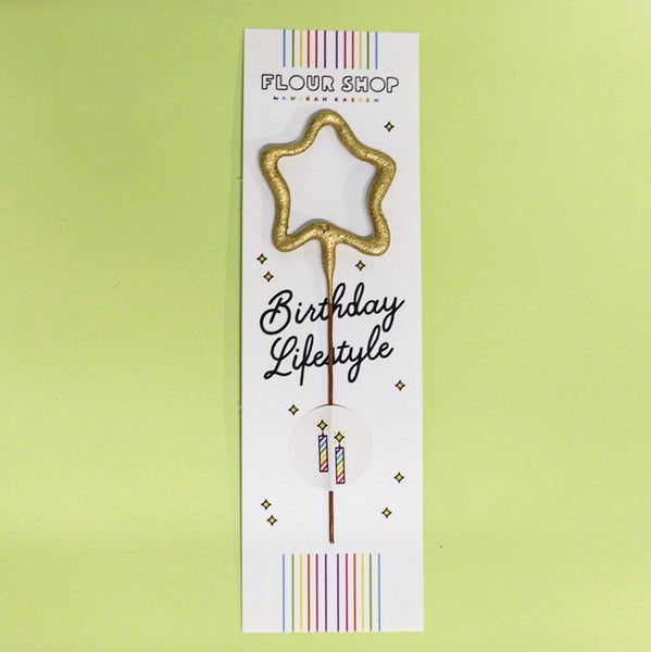 Individual mini gold star sparkler candle in FLOUR SHOP packaging