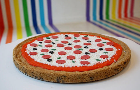 Cookie Cake decorated to look like a pizza with rainbow background