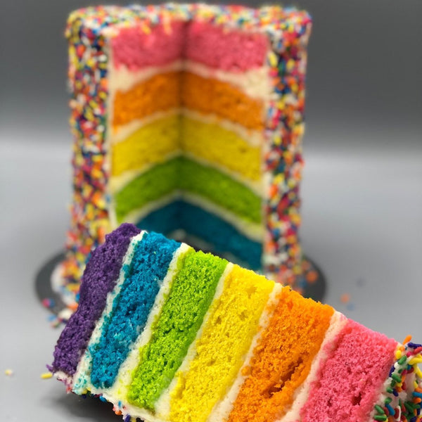 6 layer rainbow cake decorated with rainbow sprinkles