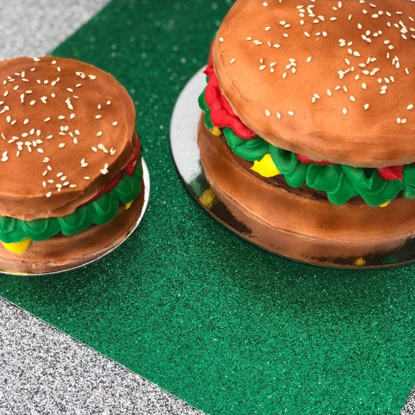 Small and large vanilla cake that is decorated to look like a cheese burger