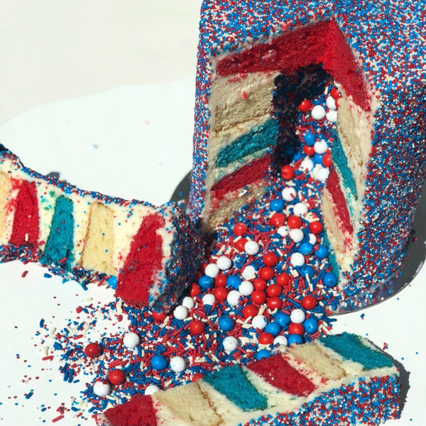 Explosion cake with 6 vanilla layers, cream cheese frosting, decorated with rainbow nonpareils and contain a red white and blue sprinkle surprise in the center with red white and blue cake layers