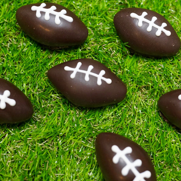 24-Pack of our Chocolate Chip Cake Balls, shaped and decorated like footballs