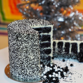 Cookies N' Cream Cake with 6 cookies n' cream layers, cream cheese frosting, decorated with black and white nonpareils and contain a sprinkle surprise in the center