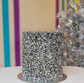Cookies N' Cream Cake with 6 cookies n' cream layers, cream cheese frosting, decorated with black and white nonpareils
