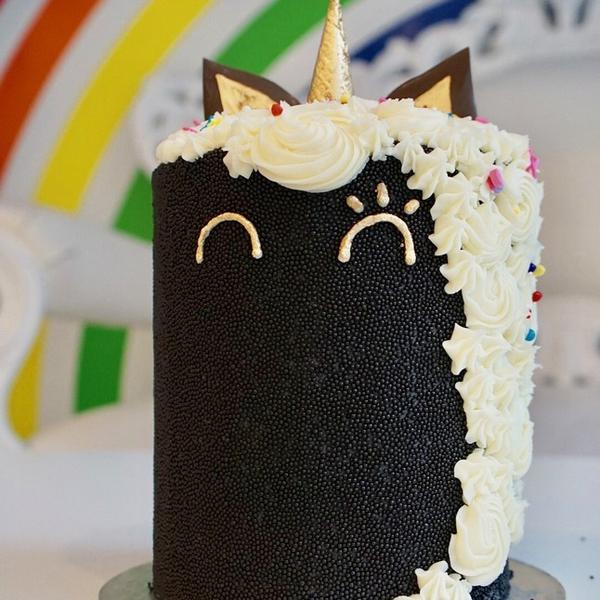 Cake decorated to look like Fabs the Unicorn - a black sprinkle cake with 6 rainbow vanilla layers, cream cheese frosting, a ice cream cone horn, chocolate ears, and contain a sprinkle surprise in the center