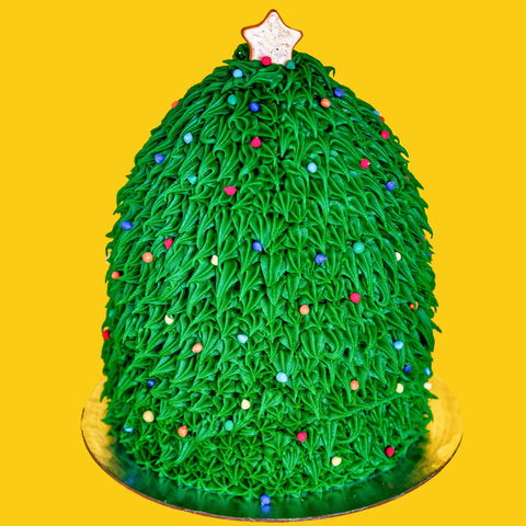 Cake in the shape of a christmas tree with gold star on top, sprinkle ornaments and piped leaf frosting