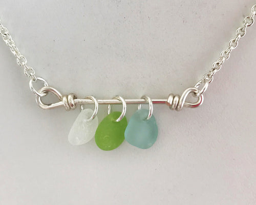 Three pieces of sea glass on silver bar