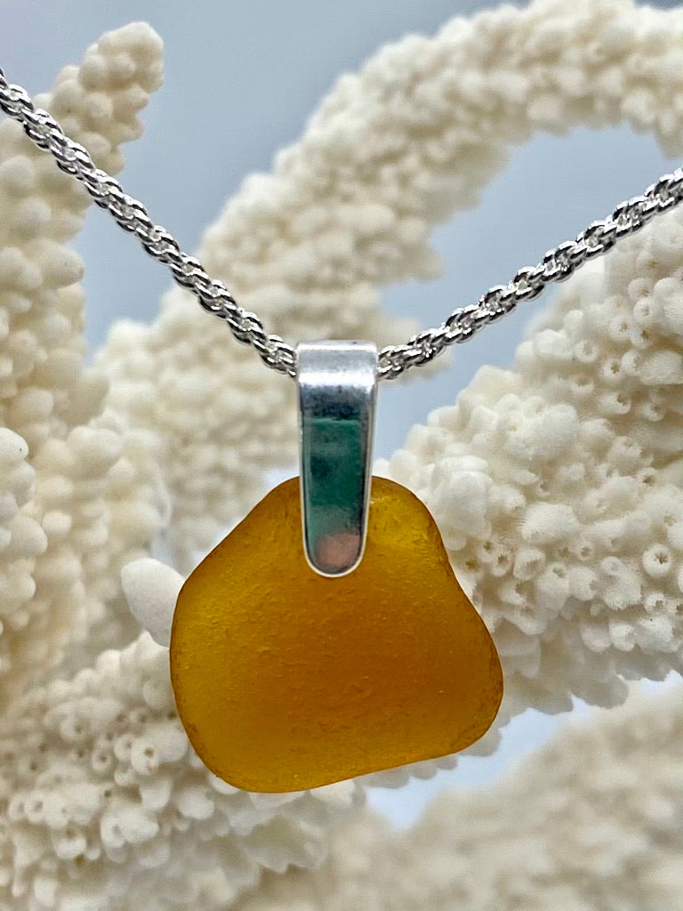 Thick piece of amber sea glass with sterling silver pinch bail
