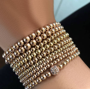 bead bracelets in a stack on arm two tone