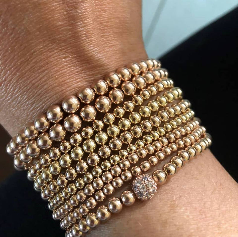 arm display of bead bracelets in rose and yellow gold